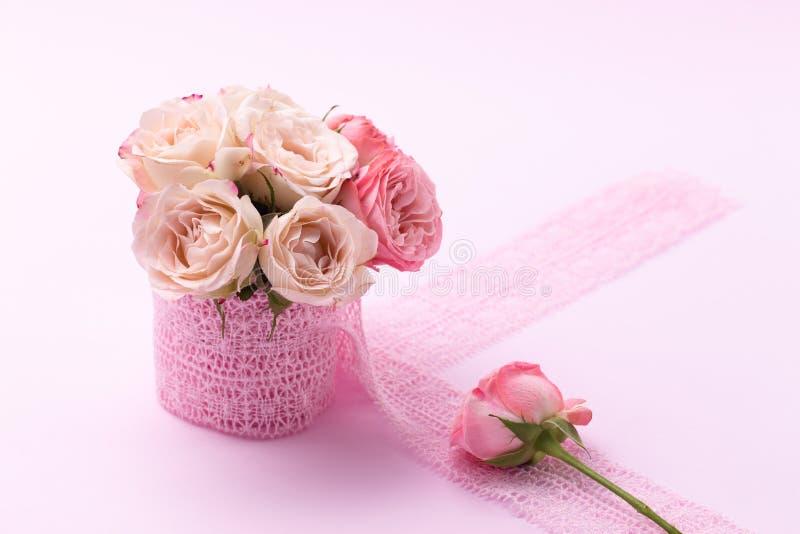 Ein Blumenstrauß von schönen Rosen steht in einem kleinen Eimer auf einem Spitzeband auf einem rosa Hintergrund mit Raum für Text lizenzfreie stockfotografie