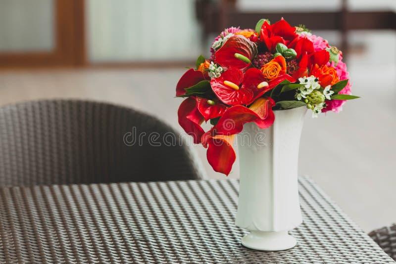 Ein Blumenstrauß von verschiedenen roten Blumen in einem Vase auf einer Tabelle Nahaufnahme gestaltungsarbeit lizenzfreies stockfoto