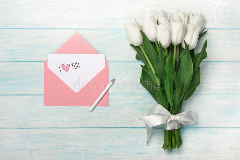 Ein Blumenstrauß von weißen Tulpen mit Liebesanmerkung und Farbumschlag auf blauen hölzernen Brettern lizenzfreie stockbilder