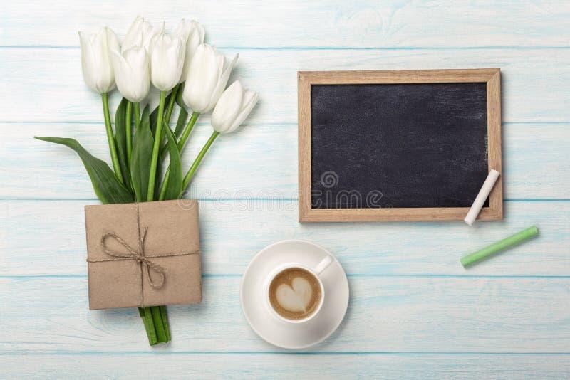Ein Blumenstrauß von weißen Tulpen, von Tasse Kaffee mit Kreidebrett und von Umschlag auf blauen hölzernen Brettern Mutter`s Tag stockbilder