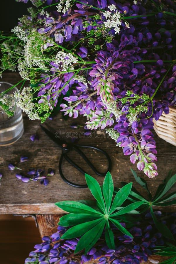 Ein Blumenstrauß von wilden Blumen auf einer Weinlesetabellen-, Dunklen und schwermütigenart lizenzfreie stockfotos