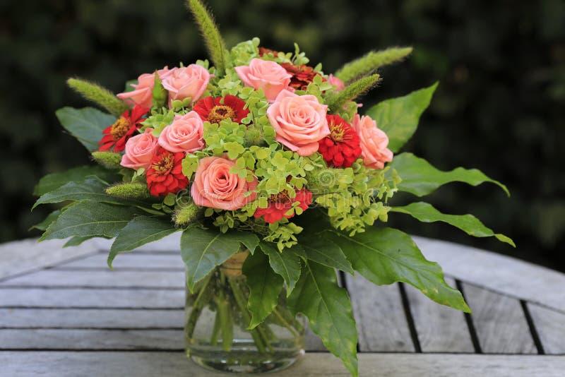 Ein Blumenstrauß mit rosa Rosen, grünen Hostas und roten Zinnias stockfoto
