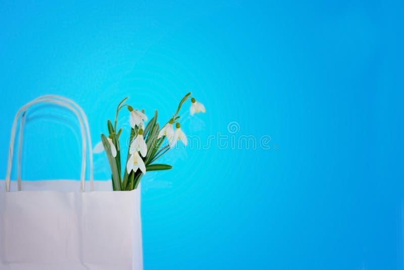 Ein Blumenstrauß von Schneeglöckchenblumen in einer Einkaufstasche lizenzfreie stockfotos