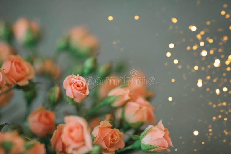 Ein Blumenstrau? von Koralle-farbigen Rosen auf einem blauen Hintergrund mit Funkeln lizenzfreie stockfotografie