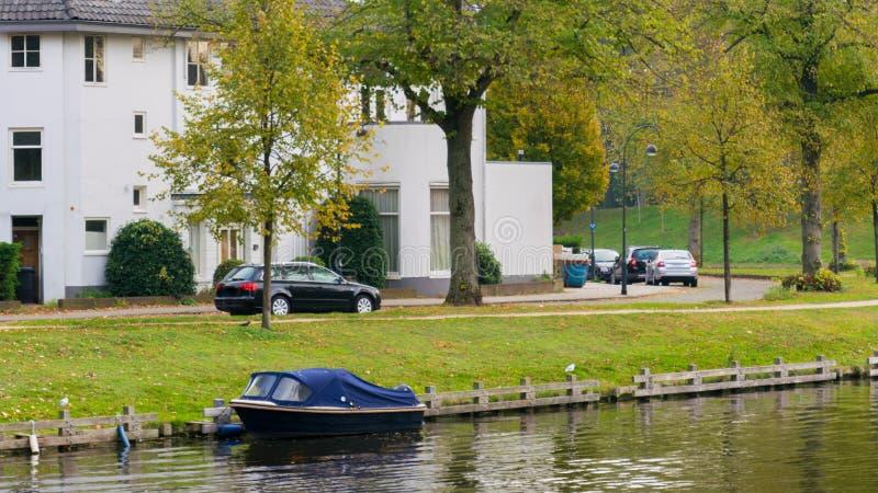 Ein Boot auf dem Stadtsee, Herbst, zusammen mit Parkplatz auf der Stra?e, den wei?en Wohngeb?uden und dem gr?nen Gras lizenzfreie stockbilder
