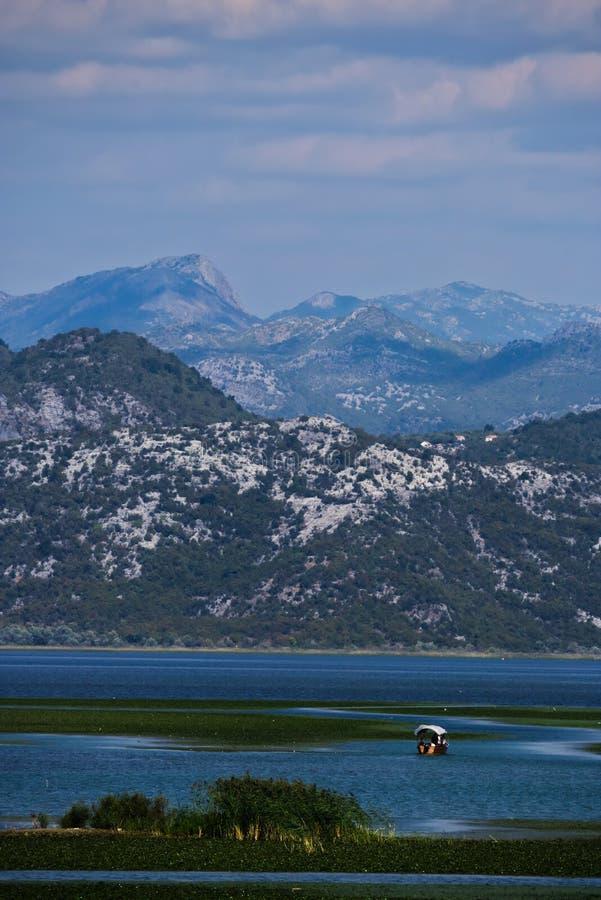 Ein Boot auf einem überwucherten See unter den Bergen stockfotos