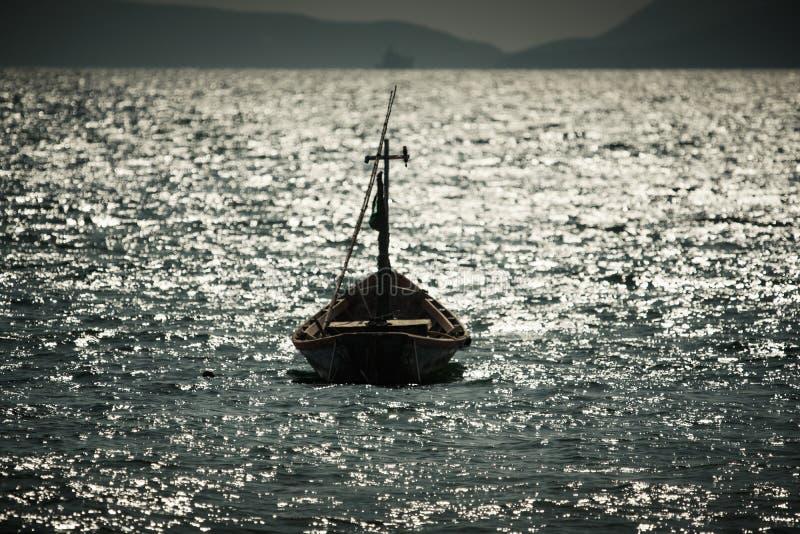 Ein Boot, das im ruhigen See verankert stockfotos