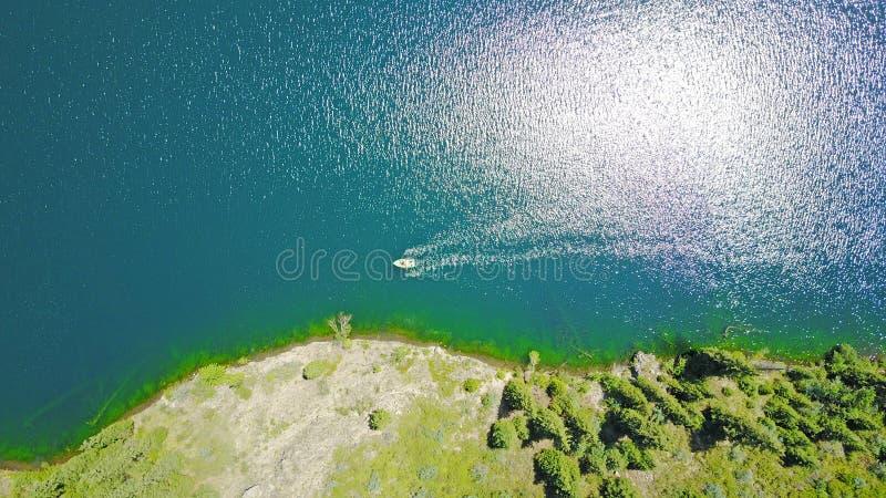 Ein Boot mitten in einem Gebirgssee Landschaftsgebirgssee im Wald stockfotos