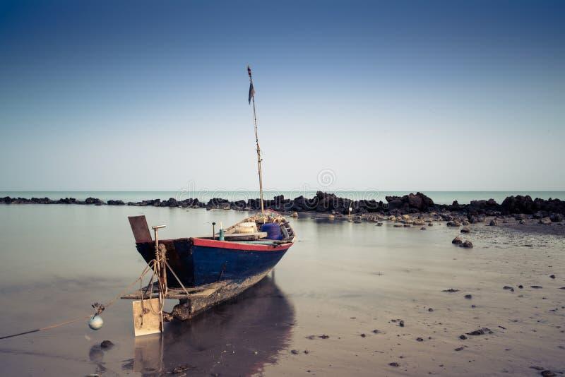 Ein Boot an Pala-Strand wenn Sonnenuntergang stockfotografie