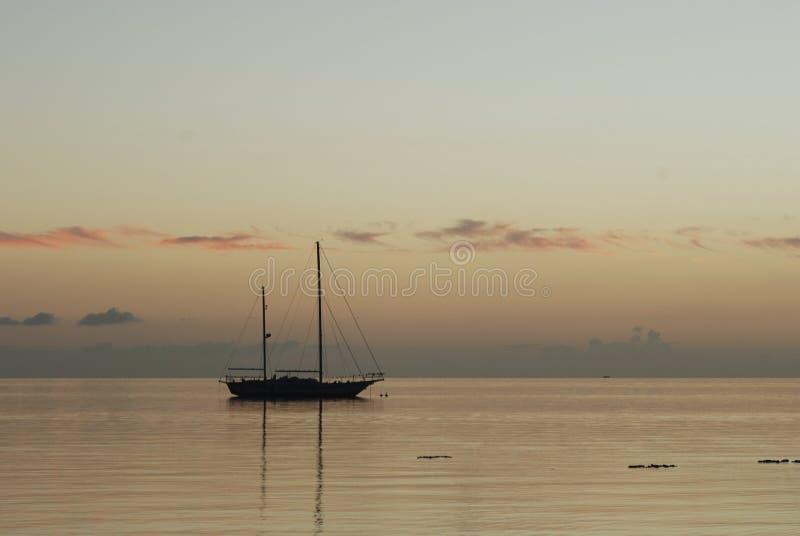 Ein Bootsschatten im tropischen Sonnenuntergang auf das Polynesien lizenzfreie stockbilder