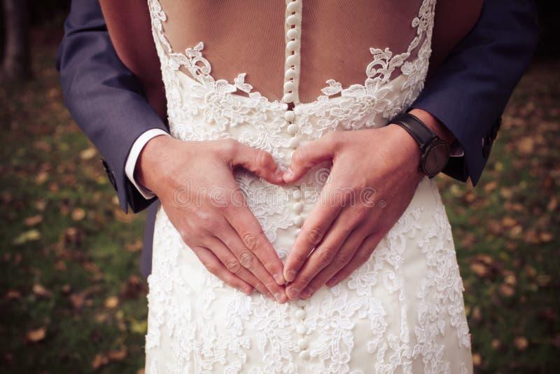 Ein Bräutigam, der eine Herzform mit seinen Händen auf seiner Frau ` s Rückseite tut stockbilder