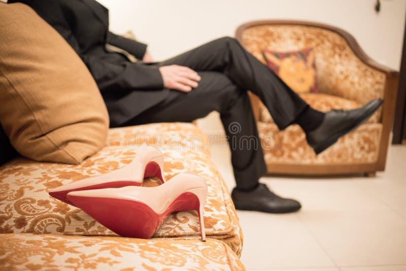 Ein Bräutigam sitzt auf dem Sofa im Hintergrund für ein Paar des Rosas hallo stockfotografie