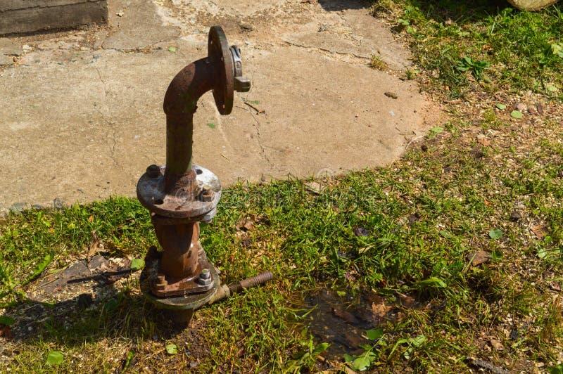 Ein Brauchwasser-Versorgungsrohr des rostigen Ätzmittels des Eisens altes für Wasserversorgung mit einem Flansch, der mit Nüssen  stockfoto