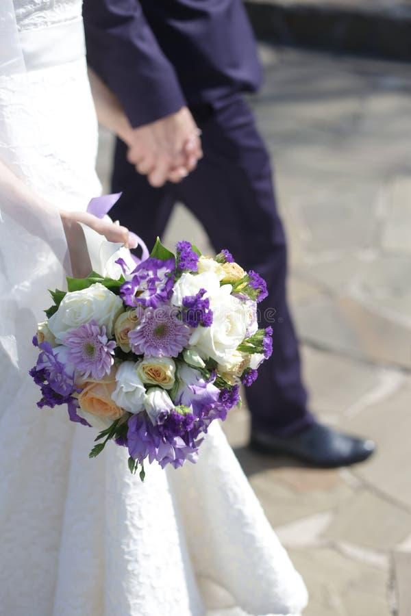 Ein Brautblumenstrauß von purpurroten, weißen und rosa Blumen, die Braut und der Bräutigam gehen durch die Hand stockfotografie