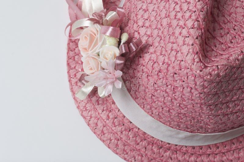 Ein breitrandiger weiblicher Hut der korallenroten Farbe, verziert mit einem Knopfloch Künstliche Blumen in Form von Rosen lizenzfreies stockbild