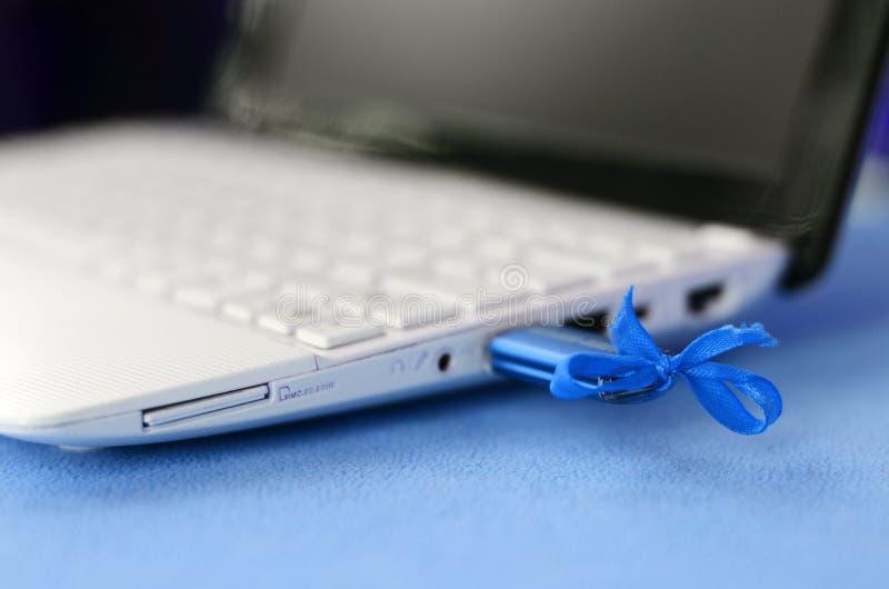 Ein Brillantblau USB-Blitz-Antrieb mit einem blauen Bogen wird an einen weißen Laptop angeschlossen, der auf einer Decke des weic lizenzfreie stockfotografie