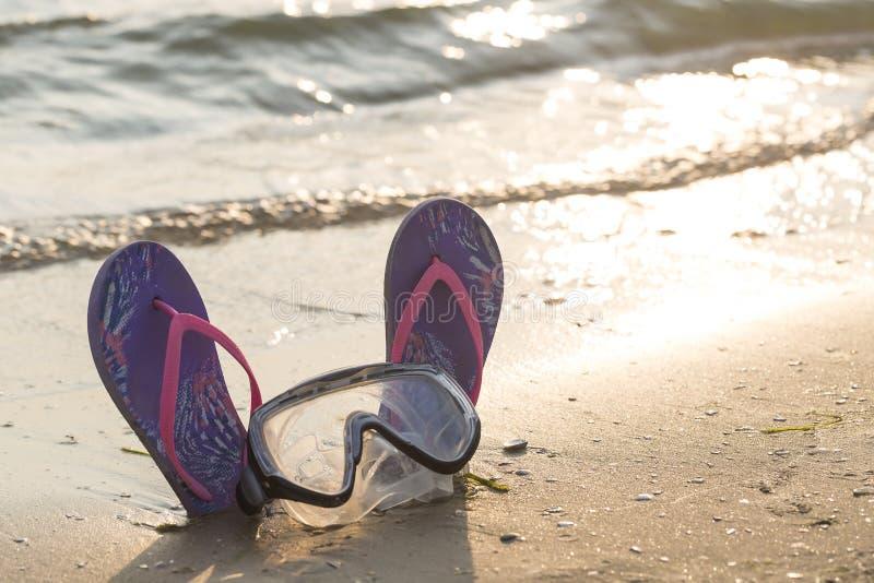 Ein britischer Paß auf einem Spielzeugstrand Bunte Flipflops mit Tauchmaske auf dem sandigen Strand während des Sonnenuntergangs lizenzfreies stockbild