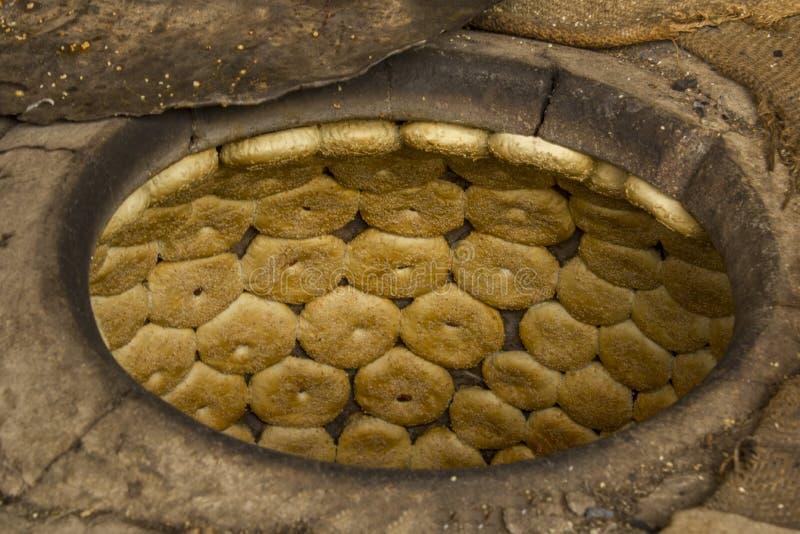 Ein Brot backt mit dem indischen Sesam zusammen, der in einem tandoor Ofen gebacken wird stockbild