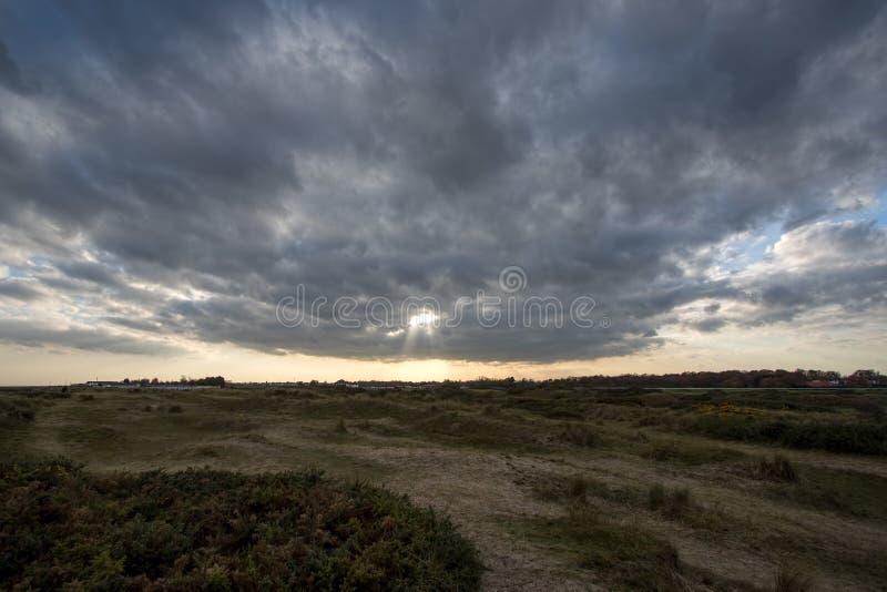 Ein Bruch in den Wolken Kahle Landschaft mit dem entfernten Sonnenbrechen stockbild
