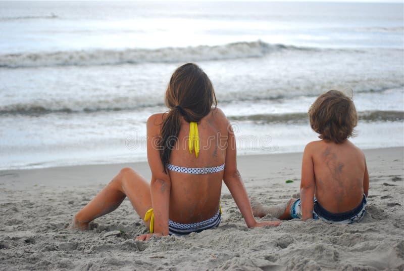 Ein Bruder und eine Schwester auf Strand anstarrend in Ozean stockbild