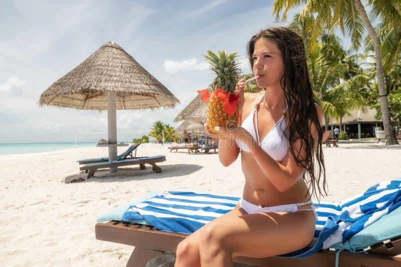 Ein Brunette in einem weißen Badeanzug sitzt auf einem Ruhesessel und trinkt ein Pina Colada-Cocktail in einer Ananas stockfoto
