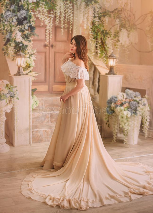 Ein brunette Mädchen in einem Sahneweinlesekleid mit offenen Schultern und mit einem langen schönen Zug Vorbildliche Aufstellung  stockfotos
