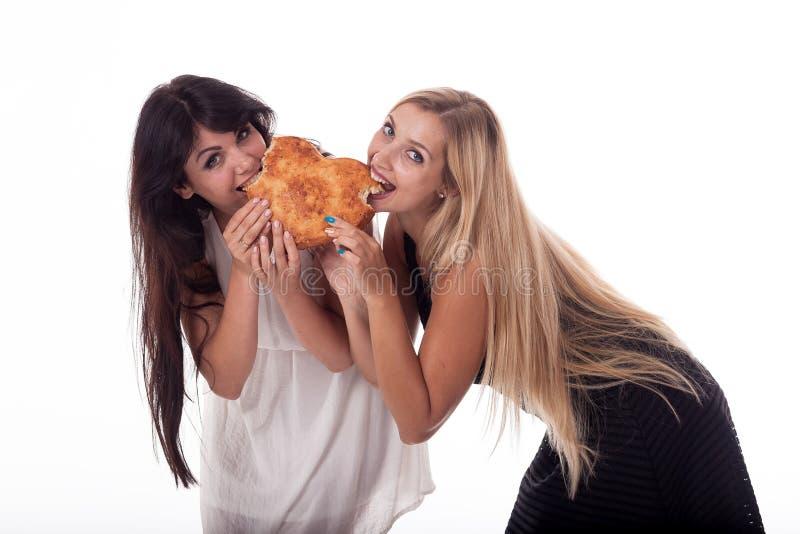 Ein Brunette und eine Blondine mit dem langen Haar beißen ein Brötchen in Form eines Herzens lizenzfreie stockbilder