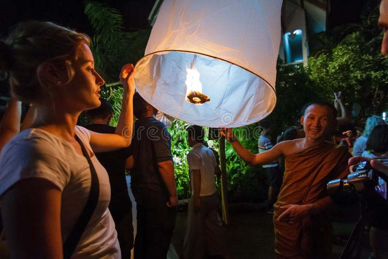 Ein buddhistischer Mönch und eine touristische Freigabe eine sich hin- und herbewegende Laterne in Chia lizenzfreies stockfoto