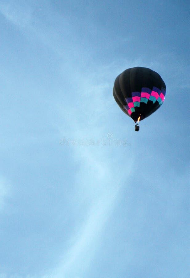 Ein bunter Heißluftballon steigt in einen azurblauen Himmel stockfoto