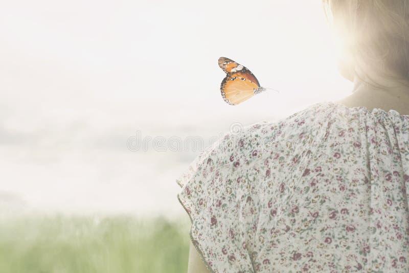 Ein bunter Schmetterling lehnt sich zart auf den Schultern eines Mädchens lizenzfreie stockfotos