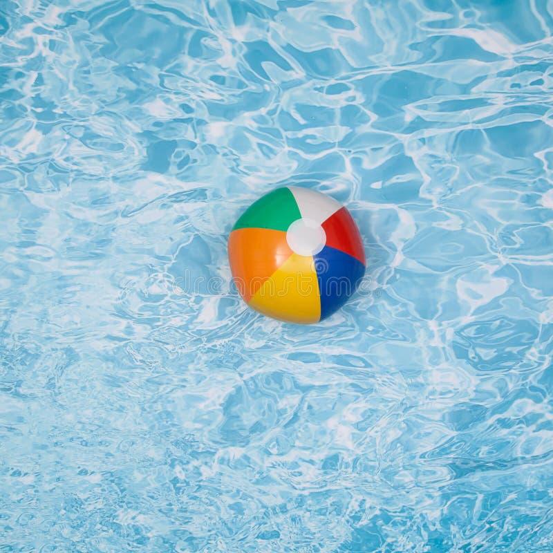 Ein bunter Wasserball, der auf den Swimmingpool schwimmt stockbilder