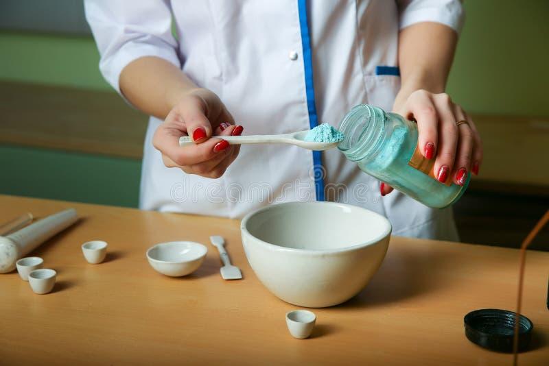 Ein Chemielehrer setzt das matereal f?r Experimente in einen M?rser stockfotos