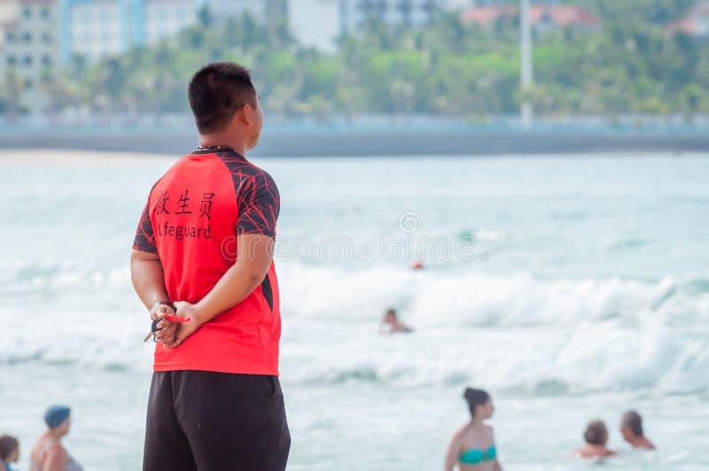 Ein chinesischer Leibwächter auf Sanya-Strand hält Auftrag und Sicherheit T-Shirt mit dem Aufschrift Leibwächter auf englisches u lizenzfreies stockfoto
