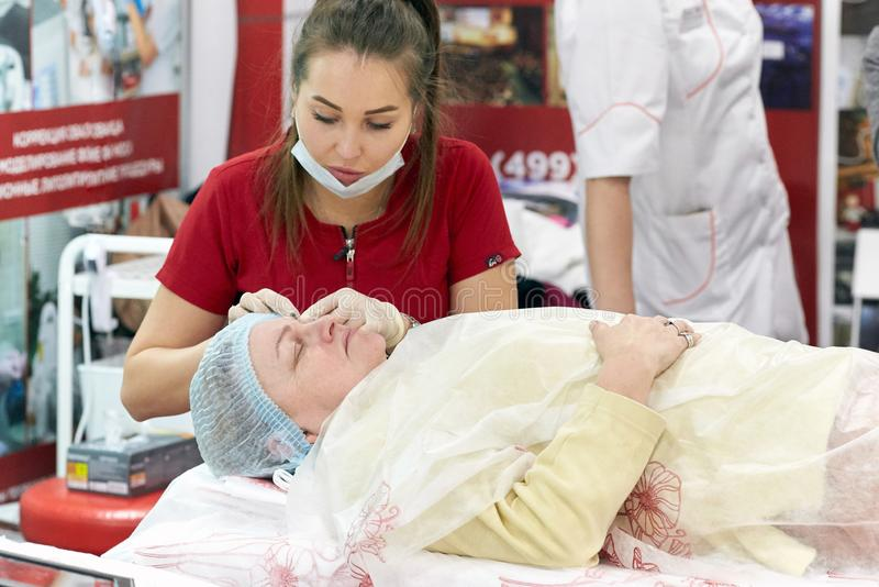 Ein Chirurgkosmetiker zeigt auf einer Frau des fortgeschrittenen Alters die Methoden der Verjüngung und des Anhebens der Haut stockbild
