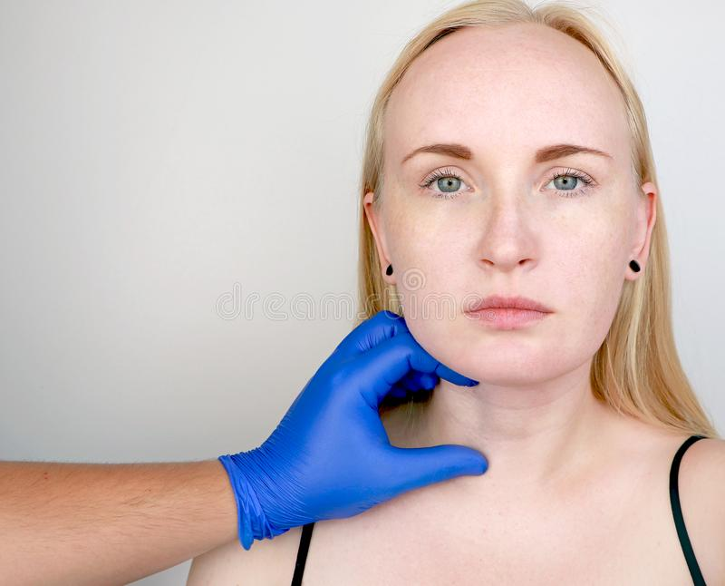 Ein Cosmetologist bereitet den Patienten für Chirurgie vor: Konturnplastik der Hals-, mesotherapy oder Botulinumtherapie Falten u lizenzfreies stockfoto