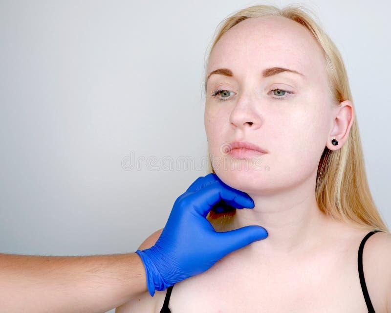 Ein Cosmetologist bereitet den Patienten für Chirurgie vor: Konturnplastik der Hals-, mesotherapy oder Botulinumtherapie Falten u lizenzfreie stockfotografie