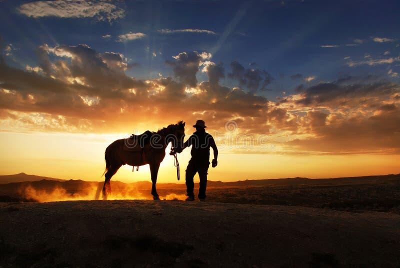 Ein Cowboy steht mit seinem Pferd stockfoto