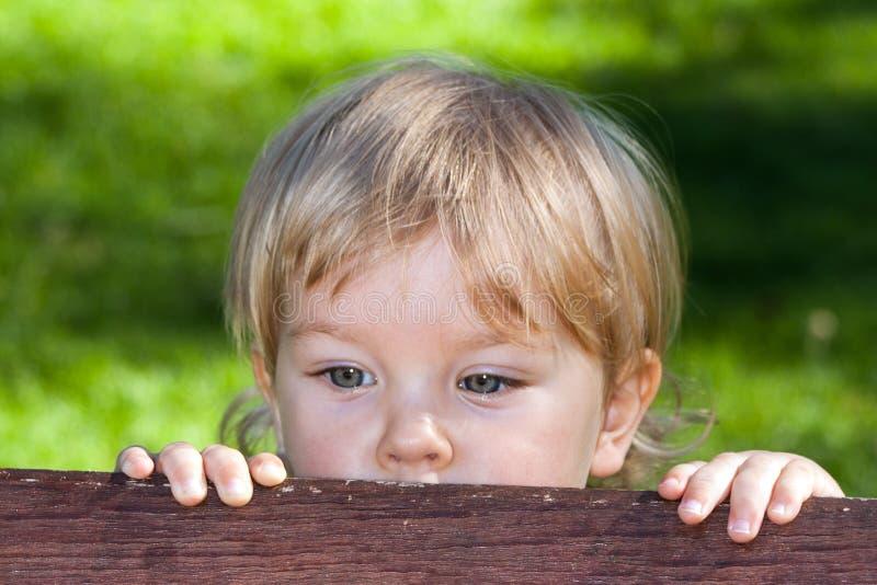 Ein curuos kleiner Junge, der hinter einer Bank sich versteckt stockbild
