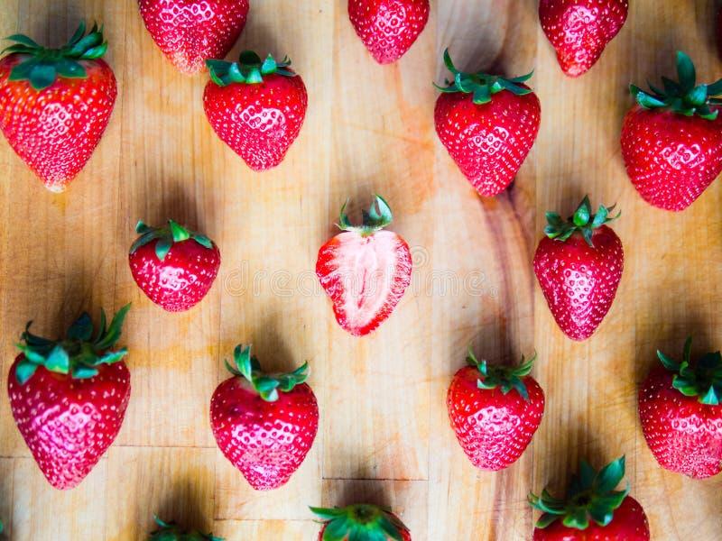 Ein cutted Erdbeere in einem srranged Muster von Erdbeeren an stockfotos