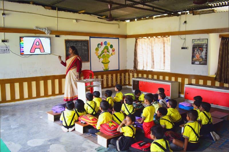 Ein Damenlehrer, der audio-visuelle Klasse von Kindergartenkindern in einem Raum nimmt lizenzfreie stockbilder
