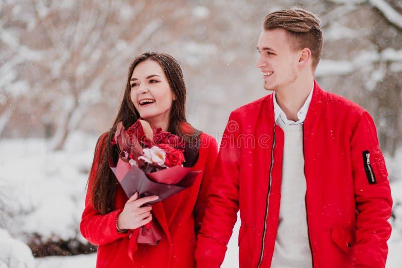Ein Datum von Liebhabern mit meinem Park im Winter Ein Blumenstrauß von roten Blumen, Weg, Umarmung, Kuss, Lachen in einer romant stockfotografie