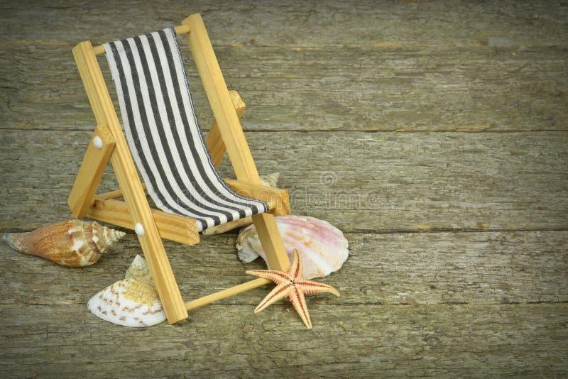 Ein deckchair und Seashells stockfotos