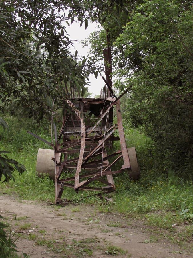 Ein defekter Metallabfalleimer steht auf einem Waldweg, der durch grüne Büsche und Bäume umgeben wird lizenzfreies stockfoto