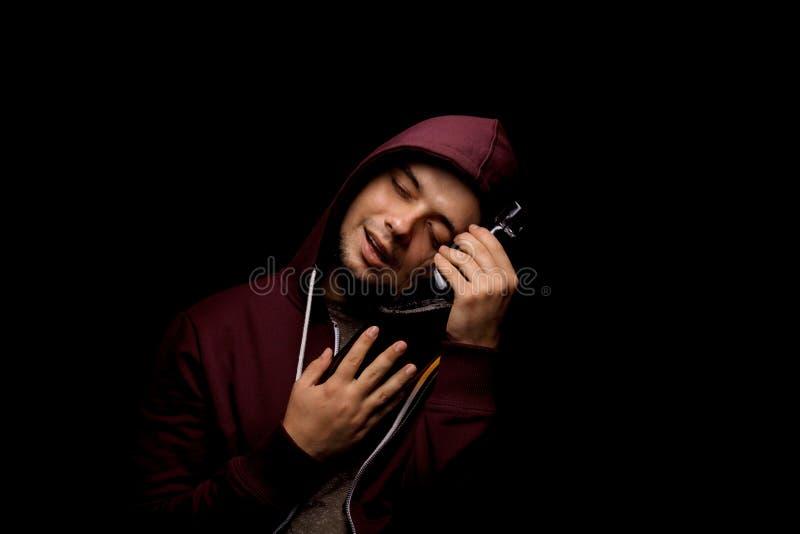 Ein defekter und einsamer alkoholischer Mann mit Krise auf einem schwarzen Hintergrund Ein Mann mit einer Flasche voll vom Alkoho lizenzfreie stockbilder