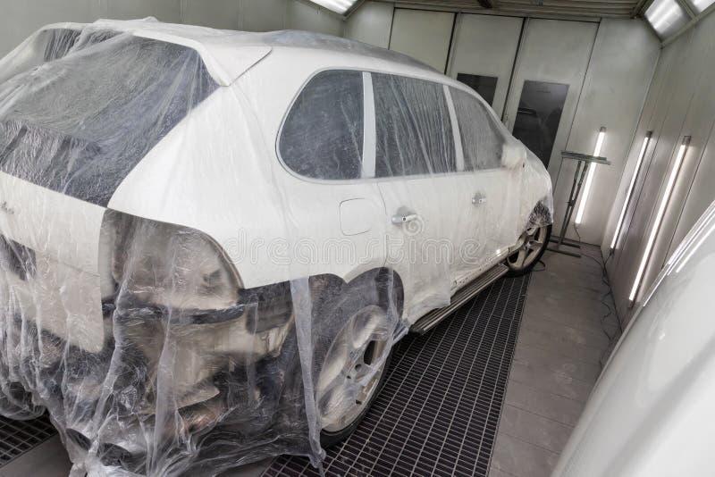 Ein defektes Auto bedeckt mit einem schützenden Film vom Spritzen der Farbe in einem Spraystand in einer FahrzeugkarosserieRepara lizenzfreie stockfotografie