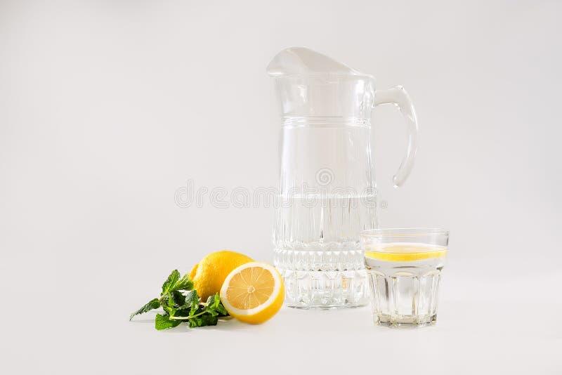 Ein Dekantiergefäß und ein Glas mit Wasser und Zitrone und Minze stockbilder