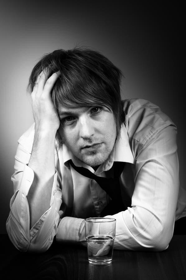Ein deprimierter junger Mann mit alkoholischem Getränk stockbild