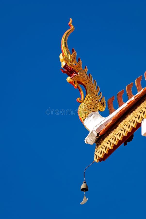 Ein Detail des thailändischen Tempelnorddachs, Naga, unter klarem blauem Himmel stockfotos