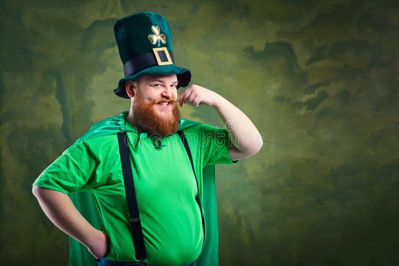 Ein dicker Mann mit einem Bart in St- Patrick` s Klage lächelt lizenzfreies stockbild