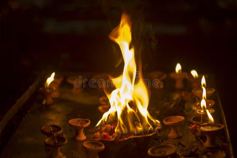 Ein Diwali-Feiertag eine Platte mit brennenden Blumen im Hintergrund von kleinen brennenden Kerzen in den Lehmständen in der Dunk lizenzfreies stockbild